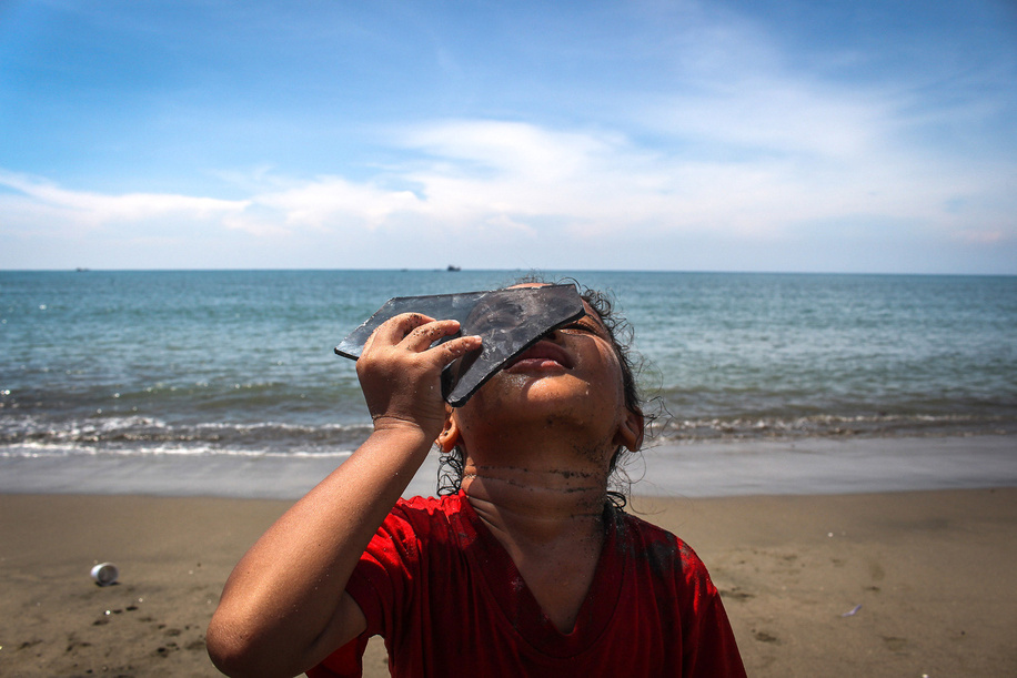 A child uses pieces of black glass to watch a partial solar eclipse on the coast of Lhokseumawe City.