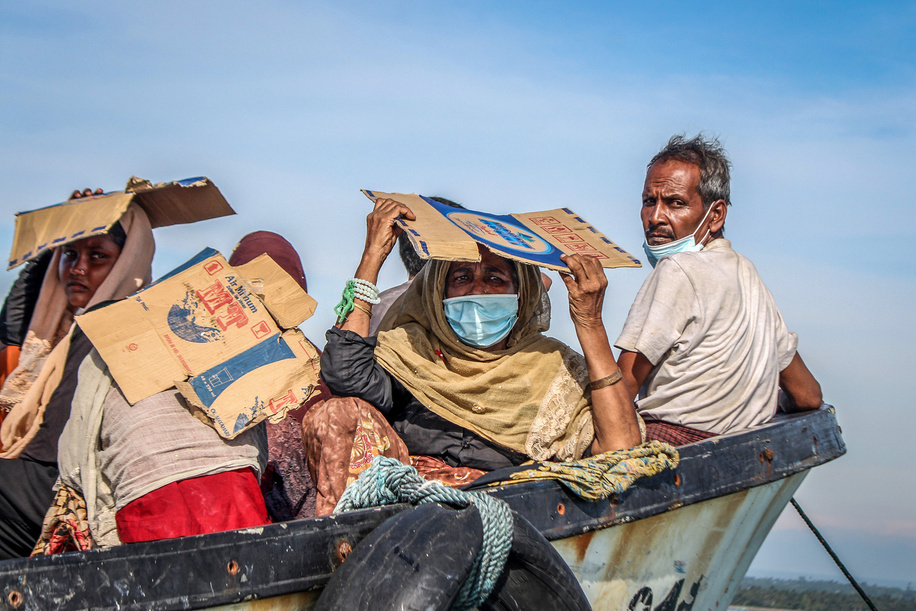 Rohingya  people seen on a stranded wooden boat using cardboard boxes to protect themselves from the sun 1 kilometre from the coast in North Aceh Regency.