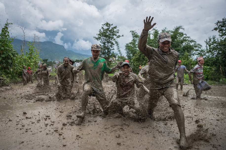 The Nepalese farmers play in mud in the rice paddy field during the National paddy day.