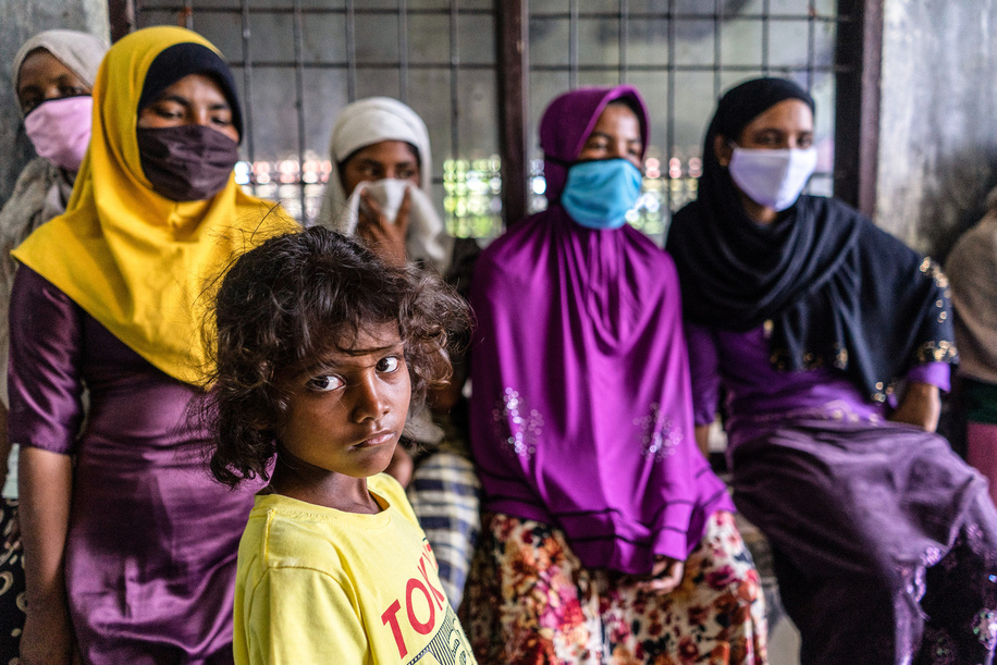 Migrant women look on at a temporary shelter in the immigration detention centre. They are among dozens of Rohingya people were rescued at sea by Indonesian fishermen while drifting on a broken boat in waters off Seunuddon in North Aceh.
