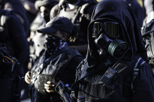Members of the Not Fucking Around Coalition (NFAC), a Black militia, stand in ranks. Breonna Taylor was killed on March 13, 2020 by Louisville Police issuing a no knock warrant to her home. The Not Fucking Around Coalition demanded the arrest of the police officers involved in Taylor's death on July 25, 2020 when they marched through town on that day. The NFAC promised they would return to Louisville if no arrests were made on behalf of Taylor. Since no progress has been made in arresting the police officers responsible for killing Taylor, the NFAC staged a demonstration in front of Churchill Downs, the site of the Kentucky Derby, to dissuade patrons from coming to the Kentucky Derby. Law enforcement met the NFAC in front of Churchill Downs, and independent Black Lives Matters protesters entered behind the NFAC making them feel claustrophobic. The NFAC relocated, and finished their demonstration at G. G. Moore Park, a few blocks away.