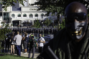 An armed member of the Not Fucking Around Coalition (NFAC), a Black militia, wears a mask while securing the flank of the NFAC. Press and civilians were pushed to edge of the grounds, while the NFAC faced law enforcement guarding Churchill Downs. Breonna Taylor was killed on March 13, 2020 by Louisville Police issuing a no knock warrant to her home. The Not Fucking Around Coalition demanded the arrest of the police officers involved in Taylor's death on July 25, 2020 when they marched through town on that day. The NFAC promised they would return to Louisville if no arrests were made on behalf of Taylor. Since no progress has been made in arresting the police officers responsible for killing Taylor, the NFAC staged a demonstration in front of Churchill Downs, the site of the Kentucky Derby, to dissuade patrons from coming to the Kentucky Derby. Law enforcement met the NFAC in front of Churchill Downs, and independent Black Lives Matters protesters entered behind the NFAC making them feel claustrophobic. The NFAC relocated, and finished their demonstration at G. G. Moore Park, a few blocks away.