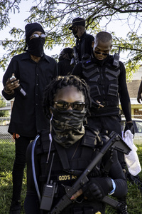 Grandmaster Jay (R), the leader of the Not Fucking Around Coalition (NFAC), a Black militia, catches his breath after moving the NFAC to a more secure location. Breonna Taylor was killed on March 13, 2020 by Louisville Police issuing a no knock warrant to her home. The Not Fucking Around Coalition demanded the arrest of the police officers involved in Taylor's death on July 25, 2020 when they marched through town on that day. The NFAC promised they would return to Louisville if no arrests were made on behalf of Taylor. Since no progress has been made in arresting the police officers responsible for killing Taylor, the NFAC staged a demonstration in front of Churchill Downs, the site of the Kentucky Derby, to dissuade patrons from coming to the Kentucky Derby. Law enforcement met the NFAC in front of Churchill Downs, and independent Black Lives Matters protesters entered behind the NFAC making them feel claustrophobic. The NFAC relocated, and finished their demonstration at G. G. Moore Park, a few blocks away.
