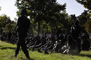 Armed members of the Not Fucking Around Coalition (NFAC), a Black militia, sit and wait for Grandmaster Jay, their leader's, instruction. Breonna Taylor was killed on March 13, 2020 by Louisville Police issuing a no knock warrant to her home. The Not Fucking Around Coalition demanded the arrest of the police officers involved in Taylor's death on July 25, 2020 when they marched through town on that day. The NFAC promised they would return to Louisville if no arrests were made on behalf of Taylor. Since no progress has been made in arresting the police officers responsible for killing Taylor, the NFAC staged a demonstration in front of Churchill Downs, the site of the Kentucky Derby, to dissuade patrons from coming to the Kentucky Derby. Law enforcement met the NFAC in front of Churchill Downs, and independent Black Lives Matters protesters entered behind the NFAC making them feel claustrophobic. The NFAC relocated, and finished their demonstration at G. G. Moore Park, a few blocks away.