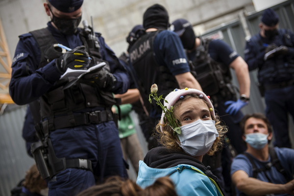 """An activist wearing a face mask with a flower is sits on the pavement during the protest. Activists from the Extinction Rebellion and ecological movement blocked the Streets of Warsaw, demanding the announcement of a """"climate alarm"""" in Poland. The police intervened. Several protesters were detained."""