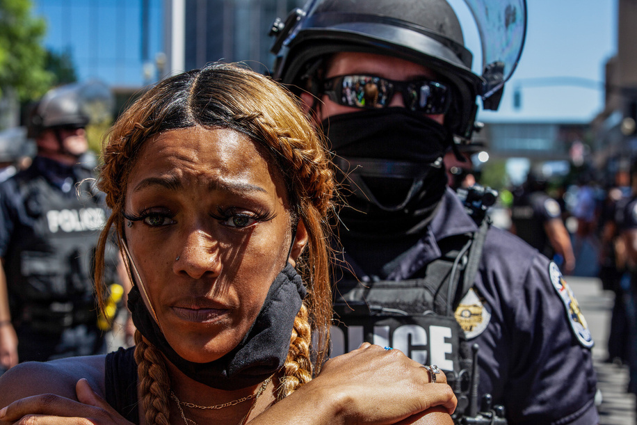 A protester in support of black lives matter stands in front of a line of Louisville Police officers during the demonstration.