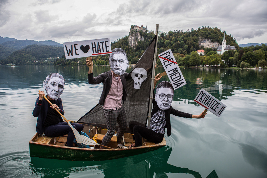 A group of protesters wearing paper masks showing the faces of Slovenian Prime Minister, Janez Jansa, Hungarian Prime Minister, Viktor Orban and Serbian president, Aleksandar Vucic row a small sailboat on Lake Bled protesting against their politics and the rise of fascism in Europe.
