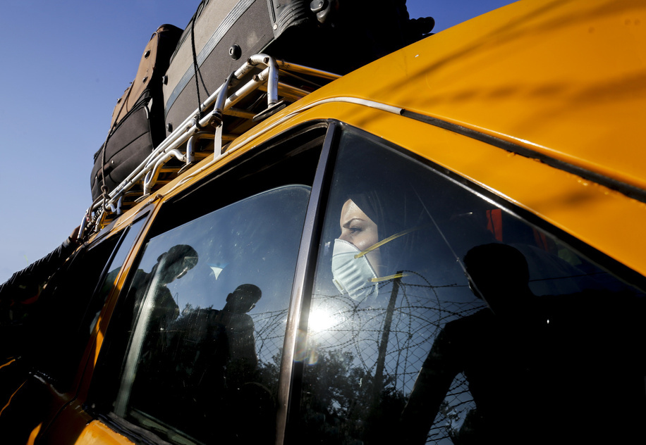 A Palestinian woman wearing a protective mask is seen inside a vehicle leaving the Rafah border crossing with Egypt. Egypt reopens the Rafah land crossing after months of closure due to the Coronavirus pandemic in the southern Gaza Strip.