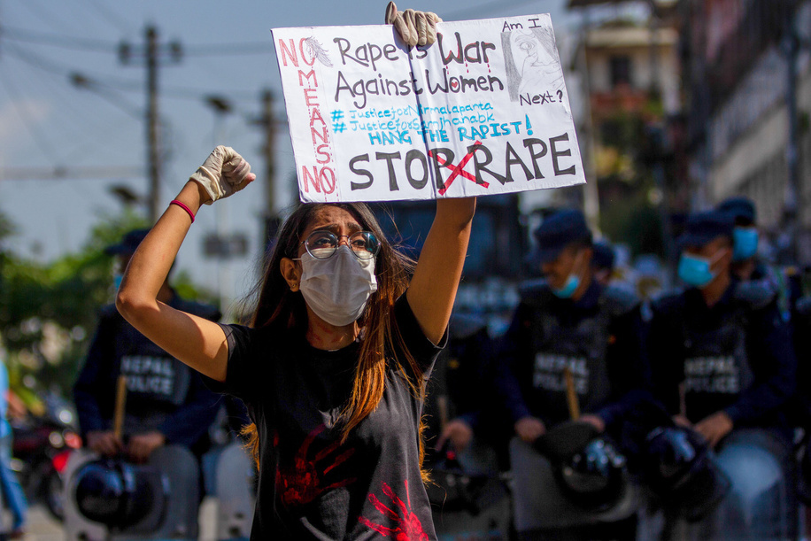 A youth holding a placard expressing her opinion while chanting slogans during a flash mob against rape.