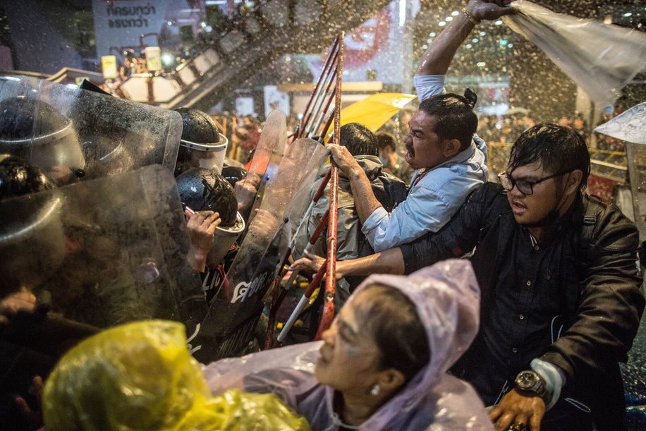 Pro-democracy protesters break through barricades as police use water cannons during an anti-government demonstration. Thousands of pro-democracy protesters took Pathumwan Intersection, one of the busiest road of Bangkok, demanding the resignation of Thailand Prime Minister and the reform of the monarchy following a 'State Of Emergency' declared by Prime Minister Prayut Chan-o-cha. The demonstration ended with clashes with pro-democracy protesters and riot police.