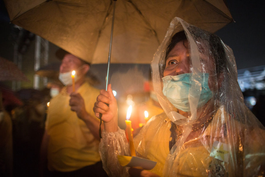 A royalist supporter wearing a raincoat and holding an umbrella to protect herself from the rain hold a candle during the fourth anniversary ceremony marking the death of late Thai King Bhumibol Adulyadej (Rama 9).