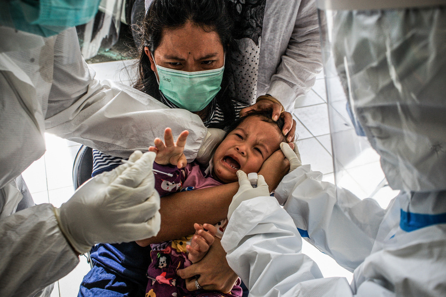 A child cries as health workers try to take a nasal swab sample from her during the Covid19 testing in Medan, North Sumatera.As Covid19 cases increase in Medan, health workers take children through swab tests and temperatures scans to curb the spread of the coronavirus.