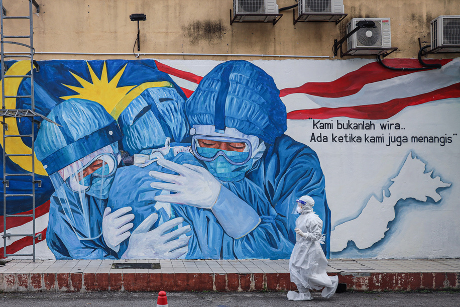 A health worker wearing a personal protective equipment walks past an alley with a mural illustrating national medical front-liners outside Clinic Ajwa in Shah Alam.