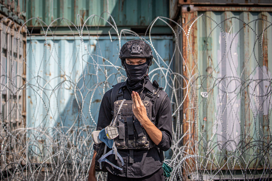 A pro-democracy protester gives the three finger salute standing in front of shipping containers and barbed wires during an anti-government demonstration in the Thai capital. Thousands of pro-democracy protesters gathered at the 14 October 1973 Memorial and accross several places in the old town to demand the resignation of Thailand Prime Minister Prayut Chan-o-cha and the reform of the monarchy. The pro-democracy protesters denounced the use of the 'Lese Majeste law' under the section 112 of the penal code as December 10 marks the 'Constitution Day' in the country.