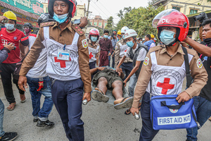 Medical team carry a wounded man on a stretcher after police and military open fire on peaceful protesters during a demonstration against the military coup. Anti-military coup protesters took to the streets of Mandalay to protest against the military coup and demanded the release of Aung San Suu Kyi. The police and military responded by firing live rounds, killing two protesters and injuring many others. Myanmar's military detained State Counsellor of Myanmar Aung San Suu Kyi on February 01, 2021 and declared a state of emergency while seizing the power in the country for a year after losing the election against the National League for Democracy (NLD).