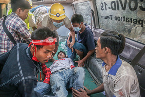 Protesters and medical team carry a wounded man into an ambulance after police and military open fire on peaceful protesters during a demonstration against the military coup. Anti-military coup protesters took to the streets of Mandalay to protest against the military coup and demanded the release of Aung San Suu Kyi. The police and military responded by firing live rounds, killing two protesters and injuring many others. Myanmar's military detained State Counsellor of Myanmar Aung San Suu Kyi on February 01, 2021 and declared a state of emergency while seizing the power in the country for a year after losing the election against the National League for Democracy (NLD).