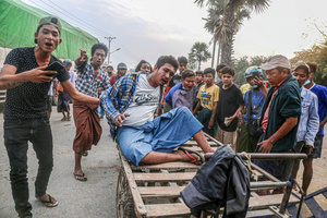 Protesters carry a wounded man on a wooden cart after police and military open fire on peaceful protesters during a demonstration against the military coup. Anti-military coup protesters took to the streets of Mandalay to protest against the military coup and demanded the release of Aung San Suu Kyi. The police and military responded by firing live rounds, killing two protesters and injuring many others. Myanmar's military detained State Counsellor of Myanmar Aung San Suu Kyi on February 01, 2021 and declared a state of emergency while seizing the power in the country for a year after losing the election against the National League for Democracy (NLD).