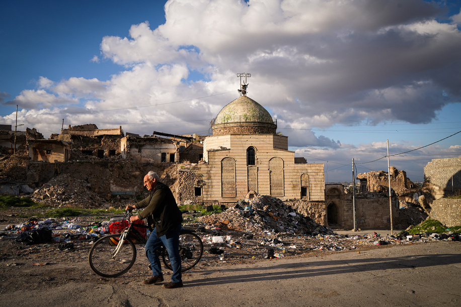 A man walks with his bicycle past the damaged mosque.