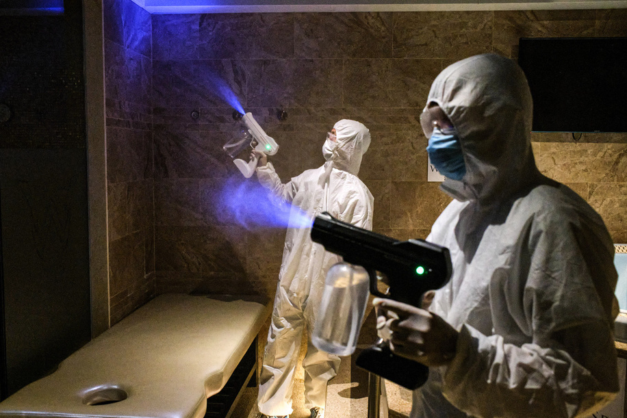 Employees wearing personal protective equipment suits (PPE) disinfect a spa facility using a disinfection Blue Light Gun during the reopening of Windsor Spa. 