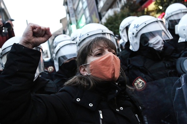 A protester shouting slogans while making gestures next to the police during the demonstration. Women gathered in Kadıkoy to protest Turkey's withdrawal from the Istanbul Convention. Turkey has pulled out of an international accord designed to protect women against domestic violence. The Istanbul Convention has caused friction within the president's party as they say it undermines family structures.