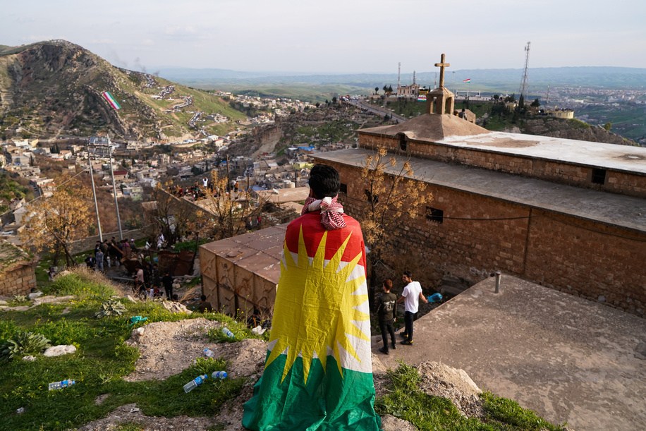 A man wrapped in a Kurdistan flag standing next to a church during the Nowruz celebration. The town of Akre in the Duhok governorate celebrated Nowruz (the Persian New Year or the Kurdish New Year).The Persian New Year or the Kurdish New Year is an old Zoroastrian tradition celebrated by Iranians and Kurds on the 20th of March of each year and coincides with the vernal equinox.