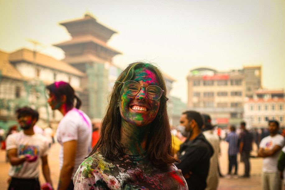 A tourist smiles as she celebrates Holi festival in Basantapur Durbar Square.