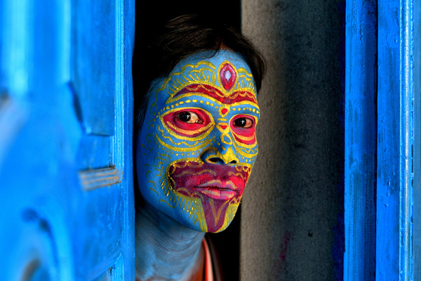 An Artist with a face paint poses for a photo prior to a Tribal Art Performance . For generations Bahurupi artists from West Bengal have been practicing the art of face painting. Using their painting techniques they can easily metamorphose into different characters during a performance, which often represent tribal myths. These traditional artists scrape a living from their performances, relying on the generosity of audiences for their income.