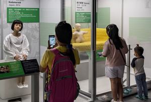 A visitor takes a photo of Japanese 'Kodomoroid' during the 'ROBOTS' exhibition at the Hong Kong Science Museum in Hong Kong on May 8, 2021. The exhibition explores the 500-year story of humanoid robots and the artistic and scientific quest to understand what it means to be human.