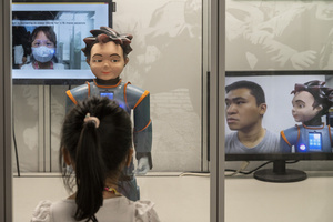 A visitor interacts with a robot during the 'ROBOTS' exhibition at the Hong Kong Science Museum in Hong Kong on May 8, 2021. The exhibition explores the 500-year story of humanoid robots and the artistic and scientific quest to understand what it means to be human.