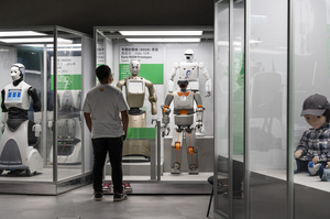 A visitor looks at different robots prototypes on displayed during the 'ROBOTS' exhibition at the Hong Kong Science Museum in Hong Kong on May 8, 2021. The exhibition explores the 500-year story of humanoid robots and the artistic and scientific quest to understand what it means to be human.