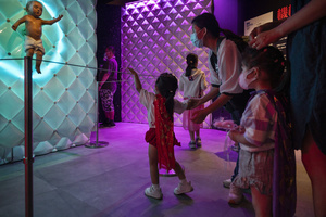A young visitor points at the 'Animatronic baby' robot during the 'ROBOTS' exhibition at the Hong Kong Science Museum in Hong Kong on May 8, 2021. The exhibition explores the 500-year story of humanoid robots and the artistic and scientific quest to understand what it means to be human.