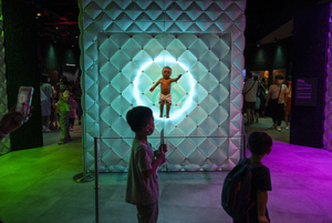 Young visitors walk past the 'Animatronic baby' robot during the 'ROBOTS' exhibition at the Hong Kong Science Museum in Hong Kong on May 8, 2021. The exhibition explores the 500-year story of humanoid robots and the artistic and scientific quest to understand what it means to be human.