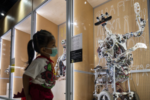 A young visitor walks past robots on displayed during the 'ROBOTS' exhibition at the Hong Kong Science Museum in Hong Kong on May 8, 2021. The exhibition explores the 500-year story of humanoid robots and the artistic and scientific quest to understand what it means to be human.