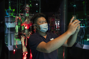 A visitor takes a selfie with the T-800 Endoskeleton robot used in filming 'Terminator Salvation' during the 'ROBOTS' exhibition at the Hong Kong Science Museum in Hong Kong on May 8, 2021. The exhibition explores the 500-year story of humanoid robots and the artistic and scientific quest to understand what it means to be human.