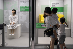 A family look at robots on displayed during the 'ROBOTS' exhibition at the Hong Kong Science Museum in Hong Kong on May 8, 2021. The exhibition explores the 500-year story of humanoid robots and the artistic and scientific quest to understand what it means to be human.