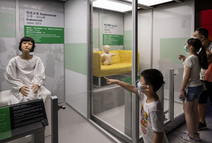 A young visitor points at the Japanese 'Kodomoroid' during the 'ROBOTS' exhibition at the Hong Kong Science Museum in Hong Kong on May 8, 2021. The exhibition explores the 500-year story of humanoid robots and the artistic and scientific quest to understand what it means to be human.