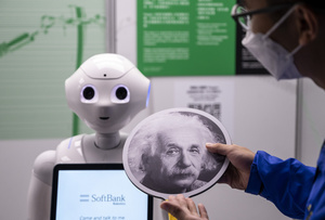 An exhibition staff holds a sign with Albert Einstein headshot  to make the robot recognize human faces at a first glance  during the 'ROBOTS' exhibition at the Hong Kong Science Museum in Hong Kong on May 8, 2021. The exhibition explores the 500-year story of humanoid robots and the artistic and scientific quest to understand what it means to be human.