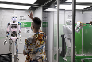 A visitor interacts with British 'RoboThespian' during the 'ROBOTS' exhibition at the Hong Kong Science Museum in Hong Kong on May 8, 2021. The exhibition explores the 500-year story of humanoid robots and the artistic and scientific quest to understand what it means to be human.