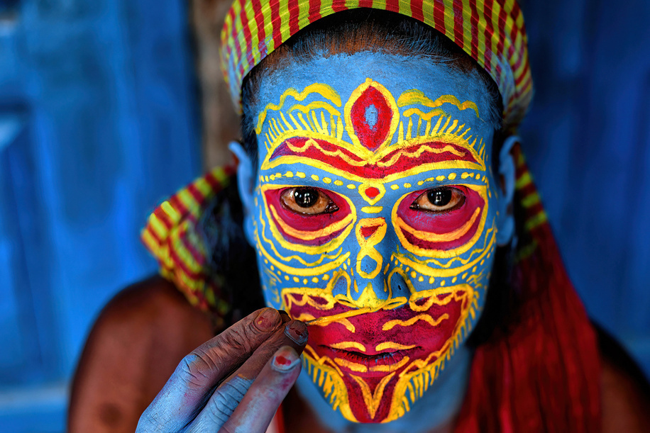 An Artist with a face paint poses for a Photo while prior to a Tribal Art Performance . For generations Bahurupi artists from West Bengal have been practicing the art of face painting. Using their painting techniques they can easily metamorphose into different characters during a performance, which often represent tribal myths. These traditional artists scrape a living from their performances, relying on the generosity of audiences for their income.
