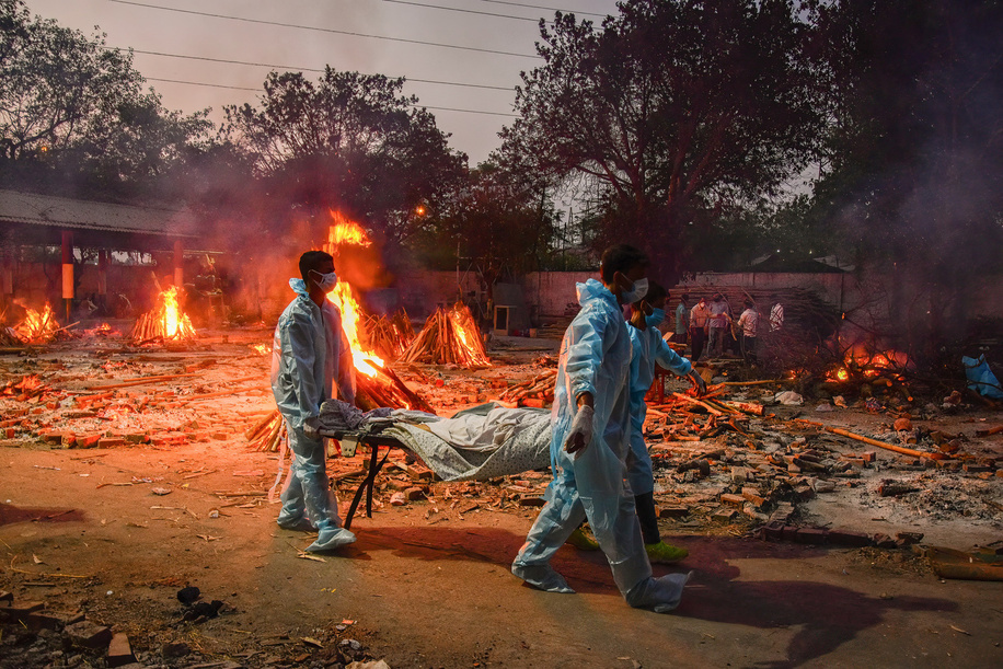 (EDITORS NOTE: Image depicts death) Workers carry the body of a person who has died of the Covid-19 coronavirus disease as other funeral pyres are seen burning during a mass cremation held at a crematorium. India has recorded a total of 19.9 million cases and 219,000 deaths since the beginning of the outbreak.