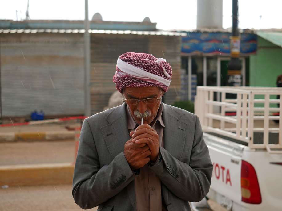 An Iraqi man lighting up his cigarette.  The lives of the people living in Northern Iraq is returning to normal after the Iraqi army has liberated the region from ISIS. Although the people are free now but it will be years until the damage can be recovered to the prewar condition.