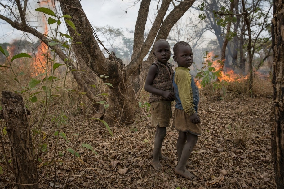 Two children stand in front of a fire their father lit to clear land for farming. Medics create prosthetics for some of the thousands of Ugandan land mine victims, who have come to Gulu Hospital, northern Uganda, since the start of the two-decade war with the Lord's Resistance Army (LRA).