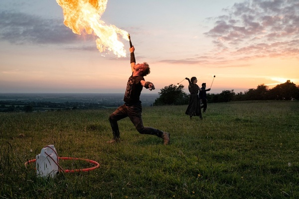 A fire breather entertains people on the Hill of Tara at the last moments before the sun sets on the longest day in the Northern Hemisphere. A large number of spectators, young and old, many accompanied with dogs, gathered at the Hill of Tara in Co. Meath to view the sunset on the June 21st Summer Solstice. The Hill of Tara is a Neolithic passage grave and is a site of important ancient historical significance in Irish folklore.