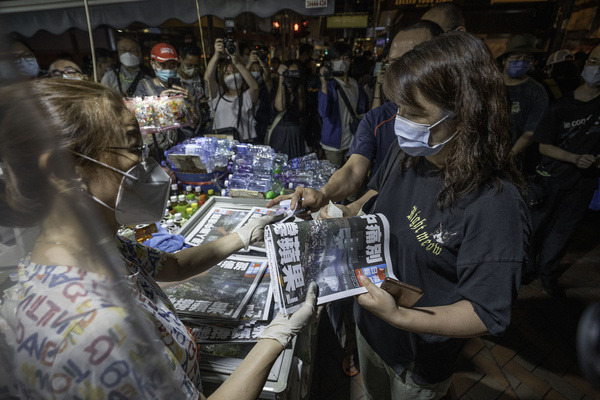 A female supporter seen purchasing a copy of the final edition of the Apple Daily newspaper at a newsstand in Mong Kok.  Pro-democracy newspaper Apple Daily will cease operation from 24th June after authorities used a national security law to arrest its top editors and freeze company assets.