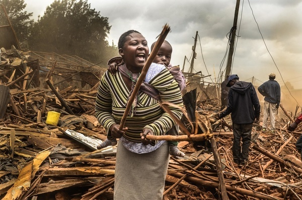 A woman with her kid on the back seen shouting at government officers after her house had been demolished. Demolition by the government to create roads and ease the traffic congestion around Nairobi left over twenty thousand families homeless in Kibera Slums. The situation also affected some Private Nongovernmental Organizations and schools around the area.