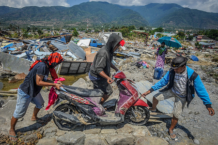 Residents took their belongings from the ruins of Balaroa village after the earthquake in Palu. A deadly earthquake measuring 7.7 magnitude and the tsunami wave caused by it has destroyed the city of Palu and much of the area in Central Sulawesi. According to the officials, death toll from devastating quake and tsunami rises to 1,347, around 800 people in hospitals are seriously injured and some 62,000 people have been displaced in 24 camps around the region.
