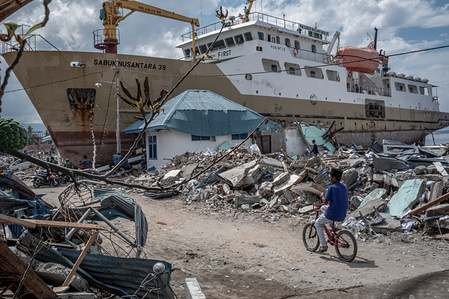 A local seen riding a bicycle next to a stranded ship. A deadly earthquake measuring 7.5 magnitude and the tsunami wave caused by it has destroyed the city of Palu and much of the area in Central Sulawesi. According to the officials, death toll from devastating quake and tsunami rises to 1,480, around 800 people in hospitals are seriously injured and some 62,000 people have been displaced in 24 camps around the region.