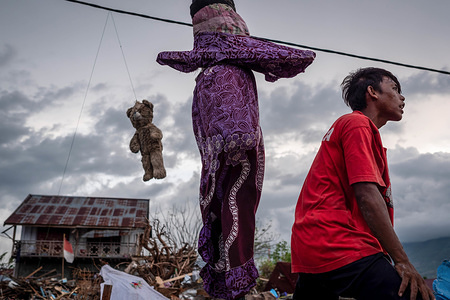 A resident seen next to a hanging teddy bear at the Lere Village after the earthquake and tsunami. A deadly earthquake measuring 7.5 magnitude and the tsunami wave caused by it has destroyed the city of Palu and much of the area in Central Sulawesi. According to the officials, death toll from devastating quake and tsunami rises to 2088, around 5000 people in hospitals are seriously injured and some 62,000 people have been displaced.