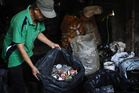 A worker separates plastic bottles collected from households and traditional markets. The waste bank manages community-based waste by handling waste as a resource that has ecological, educational and economic values so that it becomes a pilot for 3R waste management (Reuse, Reduce, and Recycle).