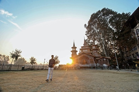 A Kashmiri resident seen walking in the park at sunset time on an autumn day in Srinagar, Indian administered Kashmir. Kashmir is the northernmost geographical region of the Indian subcontinent. It is currently a disputed territory, administered by three countries: India, Pakistan and China.